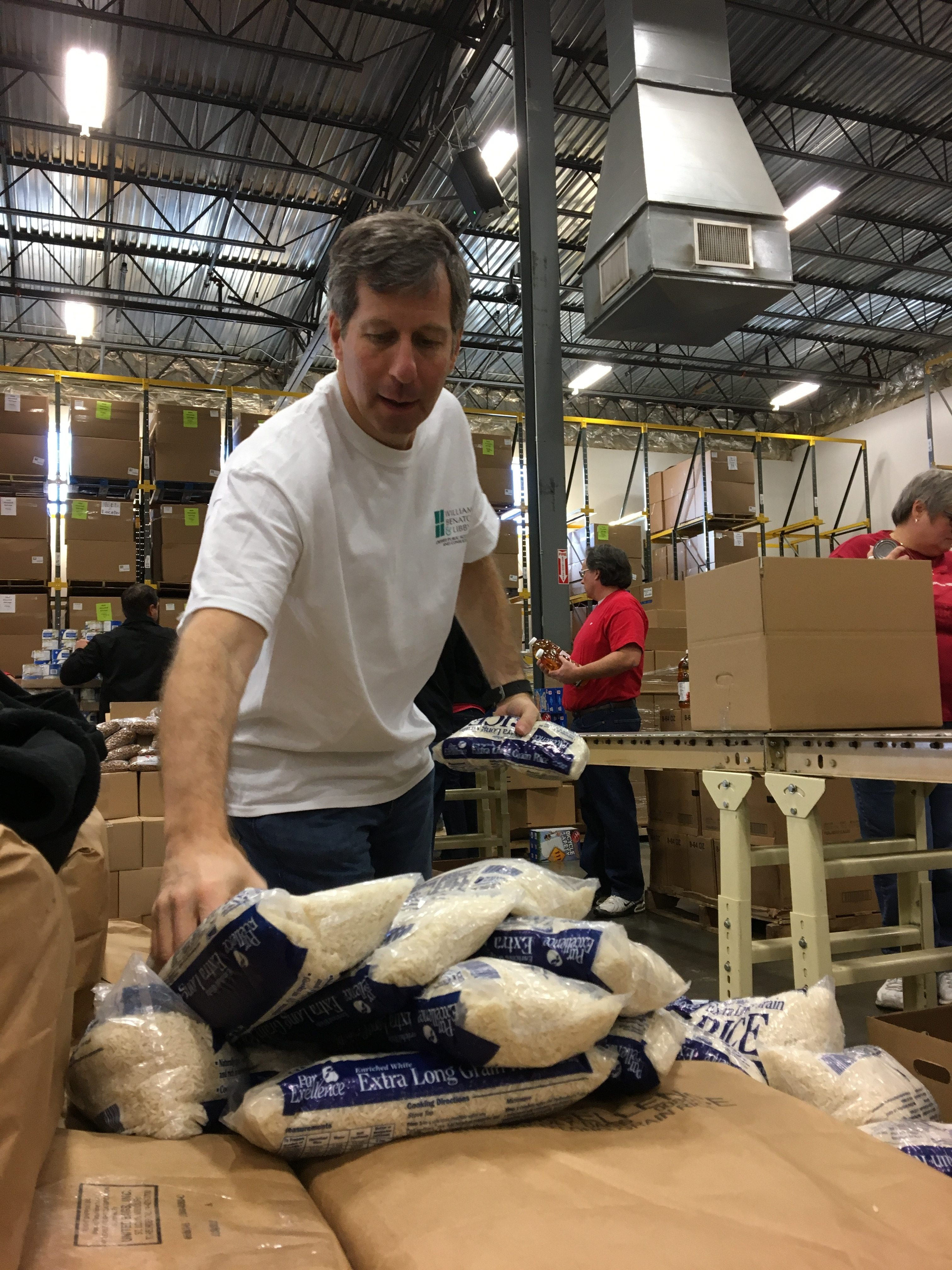 Bruce packs staples into boxes that will be delivered to Food Bank clients (ACFB 2016).